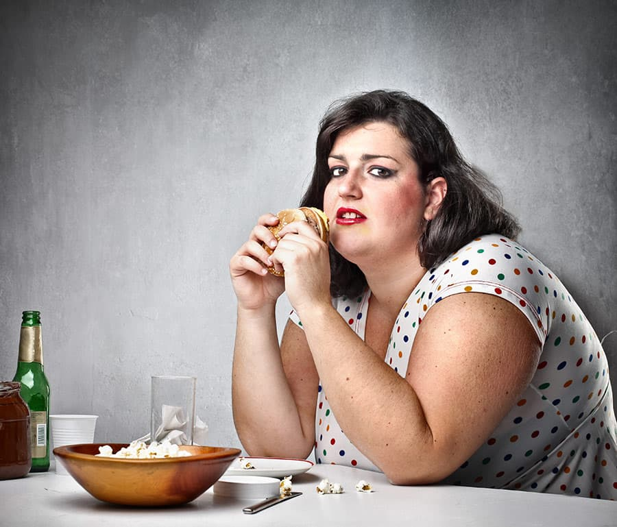 Woman eating alone, overweight and unhappy.