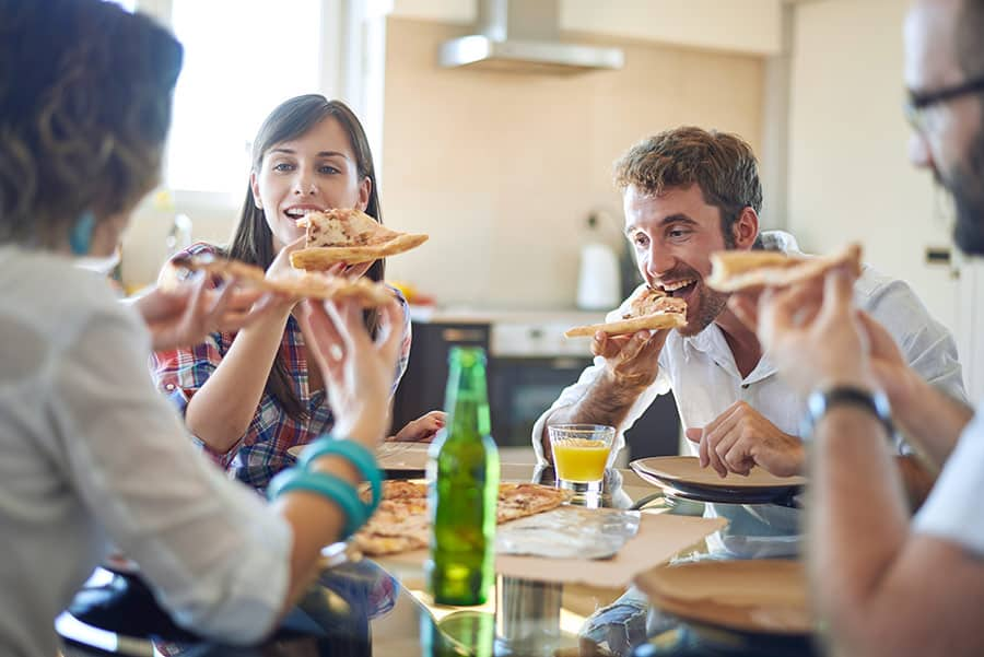Young women happily eating pizza in the company of men.